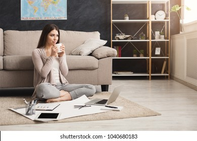 Thoughtful woman drinking coffee while working on laptop and with documents at home, sitting on the floor. Dark-haired girl in casual, copy space