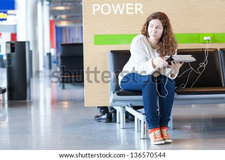 Thoughtful woman with electronic devices near place to charge your phone
