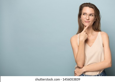 Thoughtful woman in glasses touching chin with finger, looking to left at copy space, pensive female lost in thoughts, doubtful client customer pondering sale offer, isolated on studio background