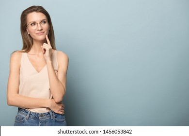 Thoughtful woman in glasses touching chin with finger, looking to right at copy space, pensive female lost in thoughts, doubtful client customer pondering sale offer, isolated on studio background