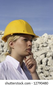 Thoughtful woman in a hard hat on a building site.