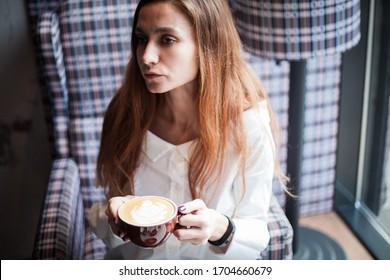 Thoughtful woman holding coffee mug in retro interior