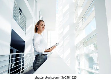 Thoughtful woman holding digital tablet and looks into the window after business meeting with partners, young successful female financier ponders over the future of company during work break in office