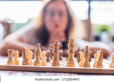 A thoughtful woman initiates strategy to play chess