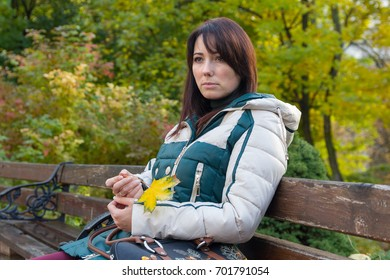 Thoughtful woman in jacket sitting on the bench. People