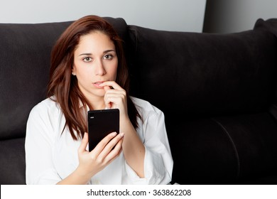 Thoughtful woman looking the mobile on the sofa at home