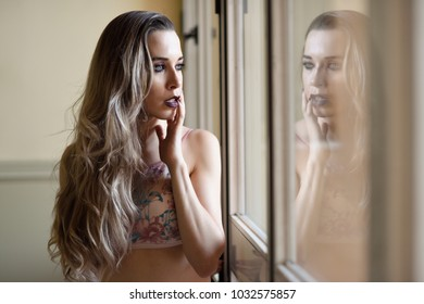 Thoughtful woman looking through the window. Beauty concept.