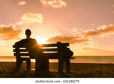 Thoughtful woman relaxing on a park bench watching the sunset.