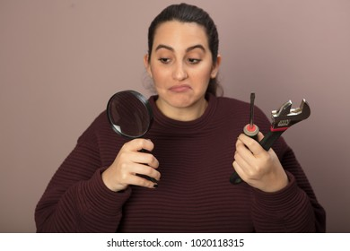 Thoughtful woman as she holds a spanner, a hammer and manifying glass in her hands in a DIY concept
