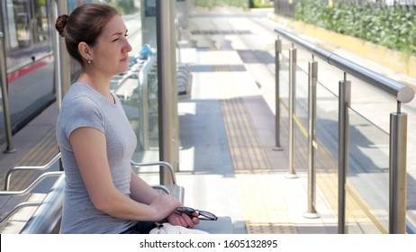 thoughtful woman sits half face on bench waiting for tramcar arrival opposite carriage door stop on hot day closeup