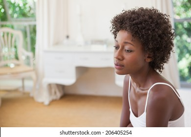 Thoughtful woman sitting on bed at home in the bedroom