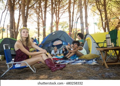 Thoughtful woman sitting on chair with friends in background at campsite