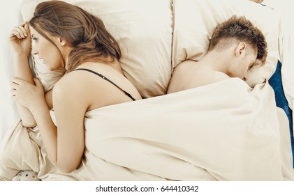 Thoughtful woman and sleeping man in bed.