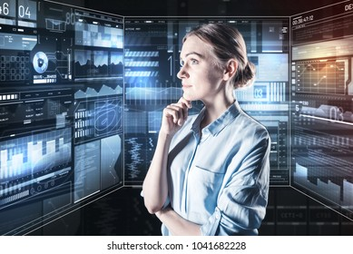 Thoughtful woman. Smart experienced calm programmer thoughtfully touching her chin and looking at the information on a transparent screen