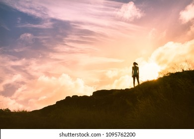 Thoughtful woman standing on mountain alone watching the beautiful sunset. People, adventure, active lifestyle concept.