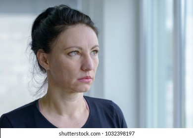 Thoughtful woman staring out of a window with a sombre deadpan expression in a head and shoulders portrait