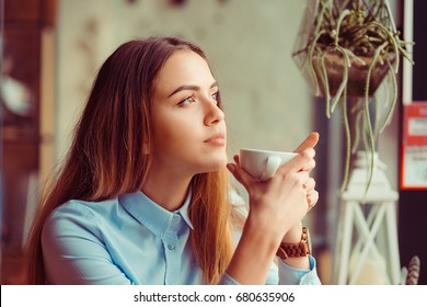 Thoughtful woman at trendy coffee shop juice bar restaurant. Young beautiful model enjoying lunch time cup of coffee tea hot drink thinking.