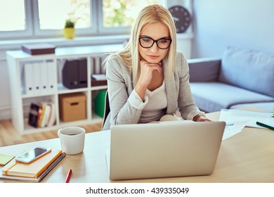 Thoughtful woman working on laptop from home