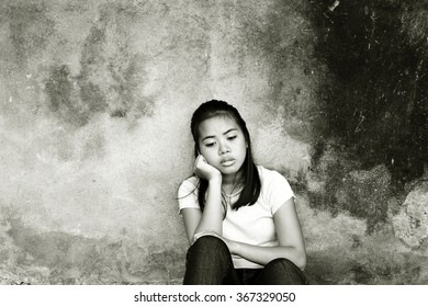 Thoughtful worried teenager sitting alone in an abandoned place