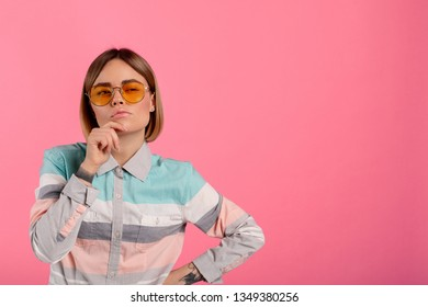 Thoughtful youbng beautiful woman look on camer and pose. She hold hand on chin. Isolated over pink background