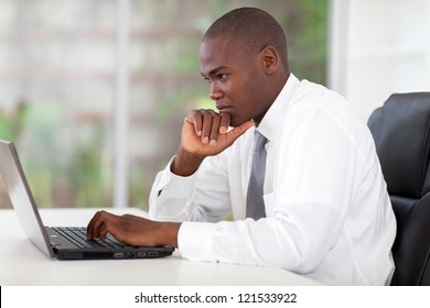 thoughtful young african american businessman working on laptop computer