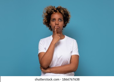 Thoughtful young african american woman holds chin, looks puzzled aside, contemplates about something. Studio shot on blue wall.