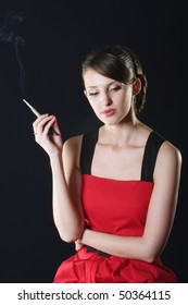 Thoughtful young attractive woman in red dress smoking