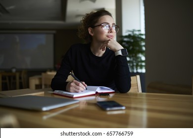 Thoughtful young author businesswoman and thinking on writing interesting article.Woman in stylish eyeglasses with good lenses look out of window and pondering new plans while noting them in notepad