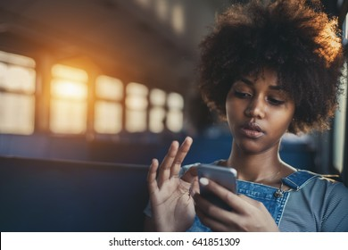 Thoughtful young biracial girl using smart phone while sitting alone in suburban train, curly african teenage female having online chat with her sister in train with copy space for your text or logo