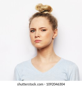 Thoughtful young blond woman against  white background, lifestyle concept