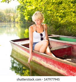 Thoughtful young blonde woman enjoying the sunny summer day on a vintage wooden boats on a lake in pure natural environment on the countryside.