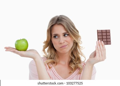 Thoughtful young blonde woman hesitating between a fruit and chocolate
