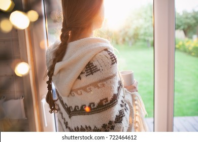 Thoughtful young brunette woman with cup of coffee looking through the window, blurry garden outside