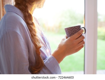 Thoughtful young brunette woman with morning cup of coffee looking through the window, blurry garden outside. Backlit by sunrise