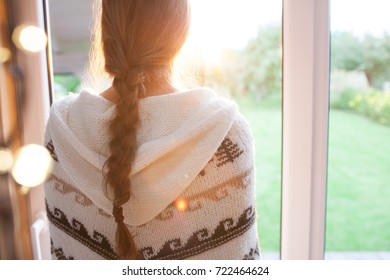 Thoughtful young brunette woman wearing nordic print poncho looking through the window, blurry garden outside