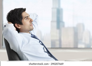 Thoughtful young business man relaxing on office chair