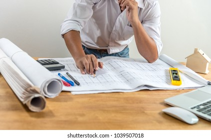 Thoughtful young businessman. Architect, engineer or interior designer standing at his desk working with laptop, blueprint, house plan or building plan.