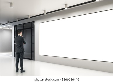 Thoughtful young businessman looking at empty poster in modern concrete interior. Gallery and museum concept. Mock up,