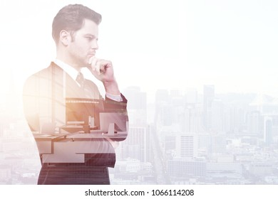 Thoughtful young businessman on abstract city background with copy space. Think and employment concept. Double exposure
