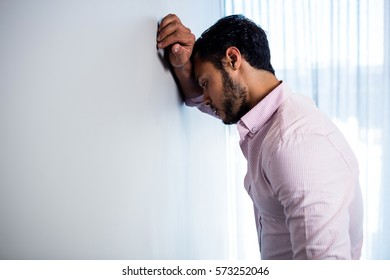 Thoughtful young businessman standing against wall in office