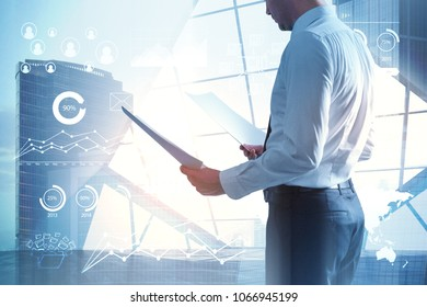 Thoughtful young businessman standing on abstract city background with digital business interface. Technology, communication and internet concept. Double exposure