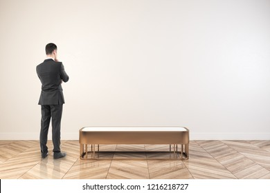 Thoughtful young businessman standing in white exhibition hall interior with empty wall. Mock up,