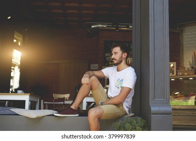 Thoughtful young businessman thinking about new design for cafe while resting on comfortable windowsill with pillows, confident forwarder waiting for employer while sitting near modern grocery store