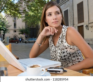 Thoughtful young businesswoman using a laptop computer and other technology while sitting down at a coffee shop terrace table, outdoors.