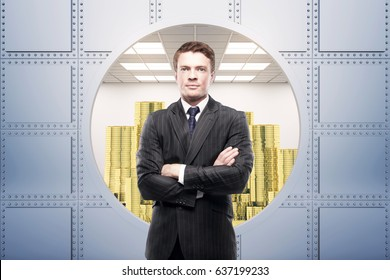 Thoughtful young european businessman in silver vault with golden coin stacks. Wealth concept.