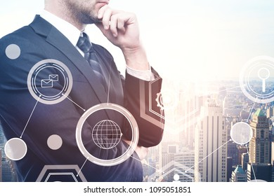 Thoughtful young european businessman standing on abstract city background with business hologram. Finance, innovation and touchscreen concept. Double exposure