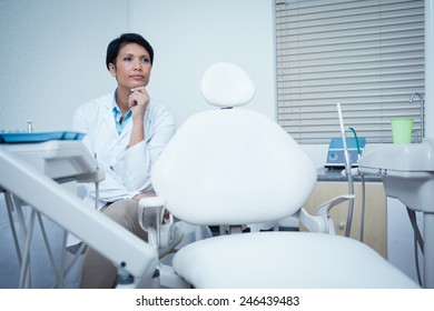 Thoughtful young female dentist looking away
