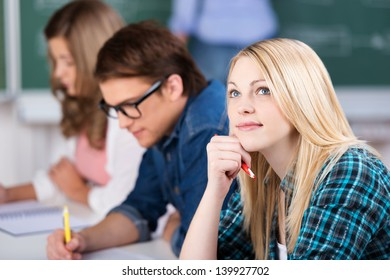 Thoughtful young female student sitting with classmates at classroom desk