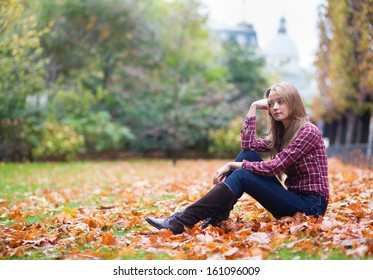 Thoughtful young girl sitting on the ground at fall