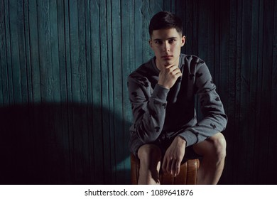 Thoughtful young handsome man with dark short hair sitting against green wooden wall in dark like and looking at you or in camera